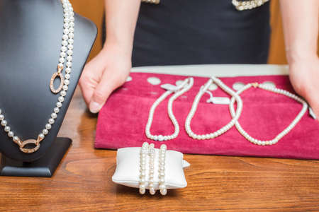 Jewelry store owner shows some pearl necklace and bracelets photo