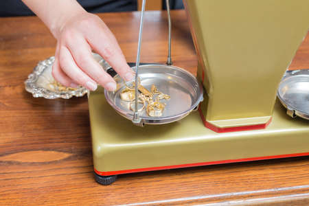 Jewelry store owner weighing gold jewelry to determine its weight and value