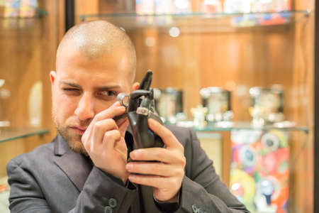Gemologist inspecting some gem-set jewelry objects with his magnifying glass photo