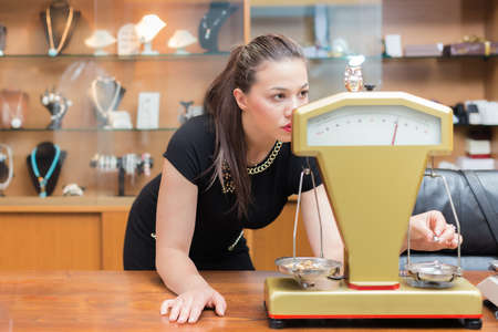Jewelry store owner weighing gold rings and necklaces to determine its weight and value. photo