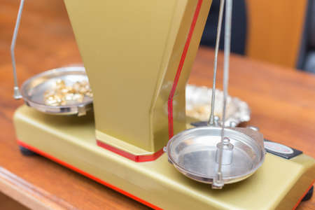 hedonism: Close-up of an old-fashioned jewelry scale, while its weighting some gold objects. Stock Photo