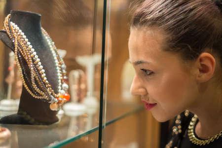 magasin: Jeune femme regardant sur la vitrine de bijoux