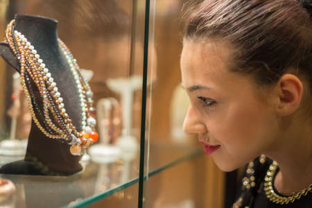 hedonism: Young woman looking on the jewelry shop window