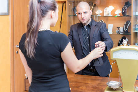 Jewelry store owner is passing a sold product to his buyer, a young woman. photo