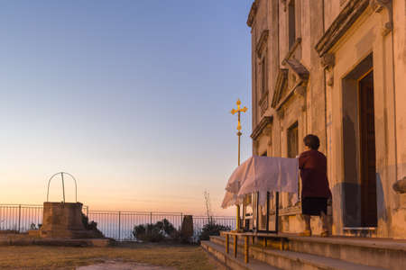 catholic mass: Capo dOrlando (Sicily), Italy - July 27, 2014 : An elderly is setting an outdoor table out of a church that will be used as an altar for a Catholic Mass