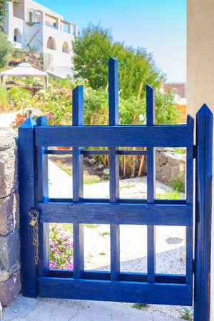 Small blue gate closed with a chain and a padlock.