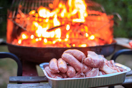 Italian sausages, lamb and sheep under them, ready to be cooked on the barbecue photo