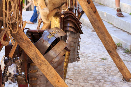 gladius: Typical object used by the Roman legions of the Roman Empire. In the picture you can see an flexible armour made up of metal strips held together with metal ties and the Gladius, the swords on the right.
