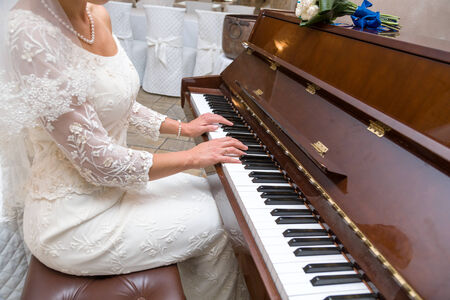 A bride is playing a piano during her wedding day photo
