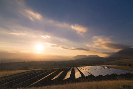 paneles solares: Foto de paisaje de una planta solar que se encuentra dentro de un valle rodeado de montañas durante la puesta de sol. Foto de archivo