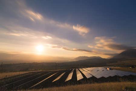 paesaggio industriale: Foto di paesaggio di un impianto solare che si trova all'interno di una valle circondata da montagne durante il tramonto.