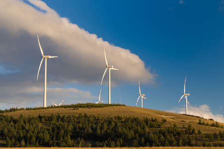 windfarm: Wind turbine power plant located over a valley. Used for producing green energy from the wind. Stock Photo