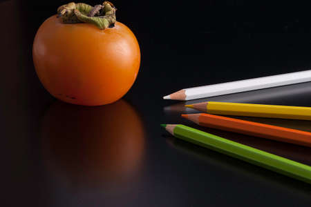 colored pencils: composition of a persimmon and colored pencils
