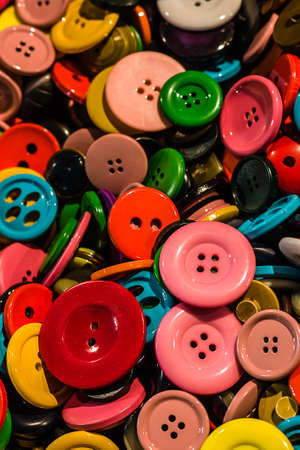 tailoring: vertical composition of colorful buttons used in haberdashery and tailoring Stock Photo