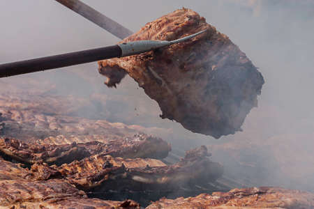 on forked: portion of grilled meat forked to be turned during cooking
