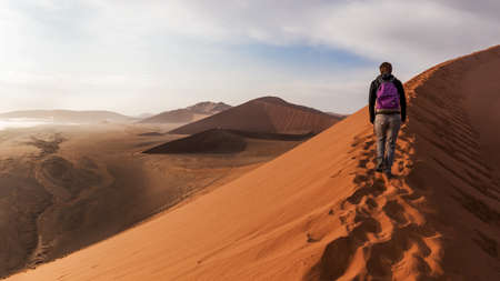 ascend: Solitary tourists up the crest of a dune in the desert of Namibia