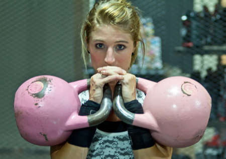 Girl posing with pink kettle bells photo