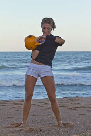 Girl using kettlebell on beach photo