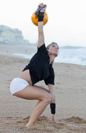 kettles: Girl using kettlebell on beach