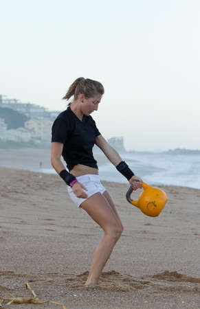 Girl doing kettlebells on the beach photo