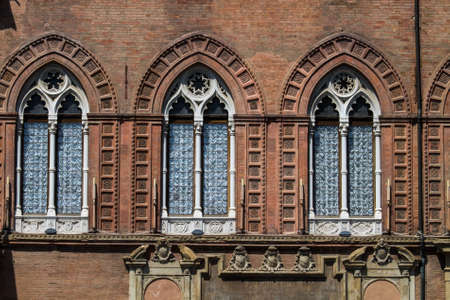 BOLOGNA, ITALY - JULY 22, 2017: Piazza Maggiore, detail of the windows of the Accursio or Comunale Palace which is the seat of the municipality - Emilia Romagna