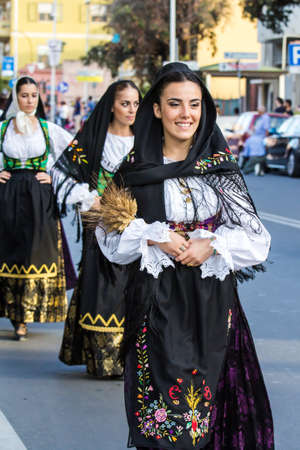 QUARTU SE, ITALY - SEPTEMBER 17, 2016: Parade of Sardinian costumes and carts for the grape festival in honor of the celebrations of Saint Helena. - Sardinia