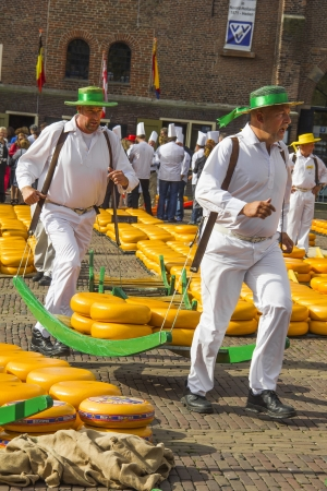 Carriers walking with many cheeses in the famous Dutch cheese market Editorial