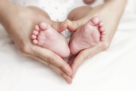 pie bebe: Pies del beb� reci�n nacido en la manos de la madre Foto de archivo