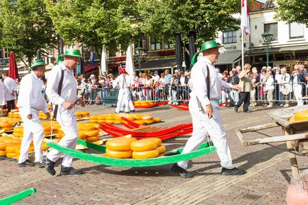 Carriers walking with famous Dutch cheeses in the cheese market in Alkmaar Editorial