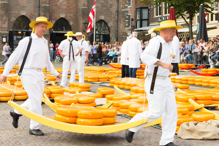 Dragers lopen met bekende Nederlandse kazen in de kaasmarkt in Alkmaar Redactioneel