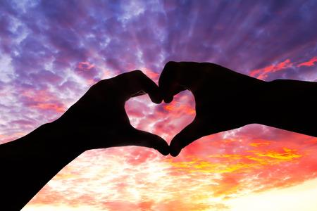 Het silhouet van de hand in hartvorm en mooie hemel