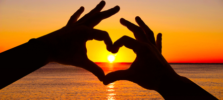valentine s day beach: Silhouette hand in heart shape and sunrise over the ocean