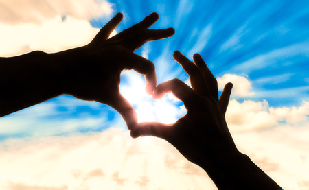 Silhouette hands in heart shape and blue sky Imagens
