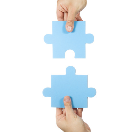 joining together: Two hands connecting puzzle pieces Stock Photo
