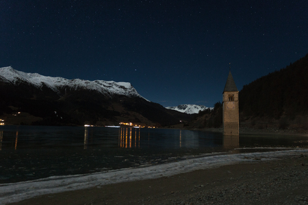 nightime: ResiaReschen, South Tyrol, Italy, 2016 - 12 10: Curon Bell tower night sight appearing from frozen lake surface, Resia, South Tyrol, Italy