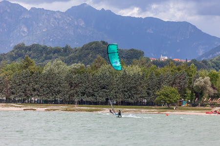 FARRA DALPAGO, ITALY  JUNE 30, 2017: 2017 windsurf world championship. Concurrents training before the race togheter kitesurfer