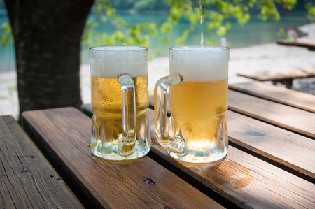 Pair of freshly filled beer glasses, over a table