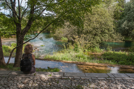 Girl watching Livenza river source, Santissima, Friuli, Italy