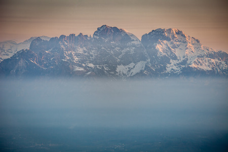 Sunrise on snow-covered Mount Schiara peaks dipped in the mist, Dolomites, Veneto, Italy