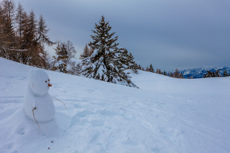 Lonely snowman with Dolomites mountains background, Col Visentin, Belluno, Italy Banco de Imagens