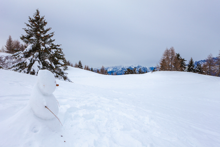 Lonely snowman with Dolomites mountains in the background, Col Visentin, Belluno, Italy 版權商用圖片 - 101600430
