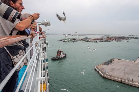 Top paddle of cruise ship with passengers observing seagulls and Venice harbor 新聞圖片