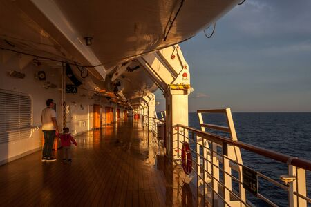 Father and son watching the sunrise from the deck of a cruise ship 版權商用圖片 - 133324433