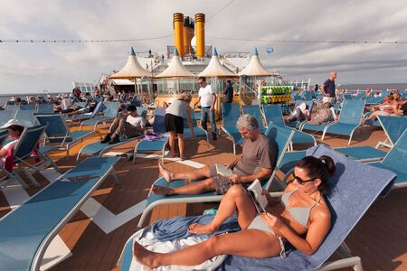 Cruise ship passengers relaxing in the sun on the upper deck 版權商用圖片 - 133324440