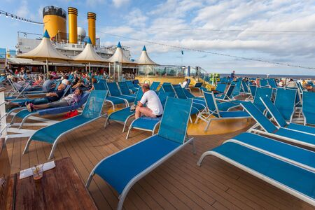 Cruise ship passengers relaxing on the upper deck