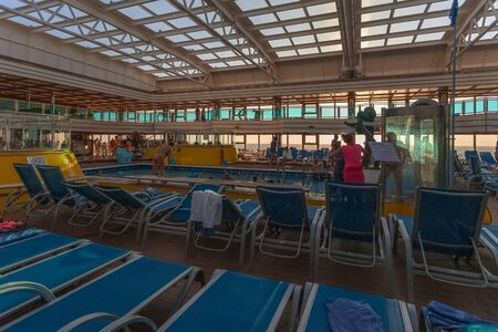 Cruise ship passengers relaxing in the swimming pool on the upper deck 版權商用圖片 - 133324447