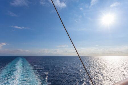 Wake left by the propellers of a cruise ship with clouds and sun at horizon