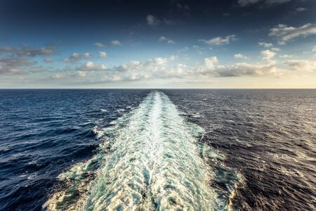 Wake left by a cruise ship with cloudy sky background