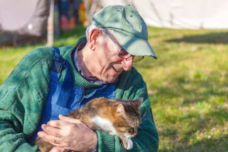 Closeup of elderly man holding his cat in his arms