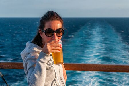 Girl drinking beer on a cruise ship deck with with sea background